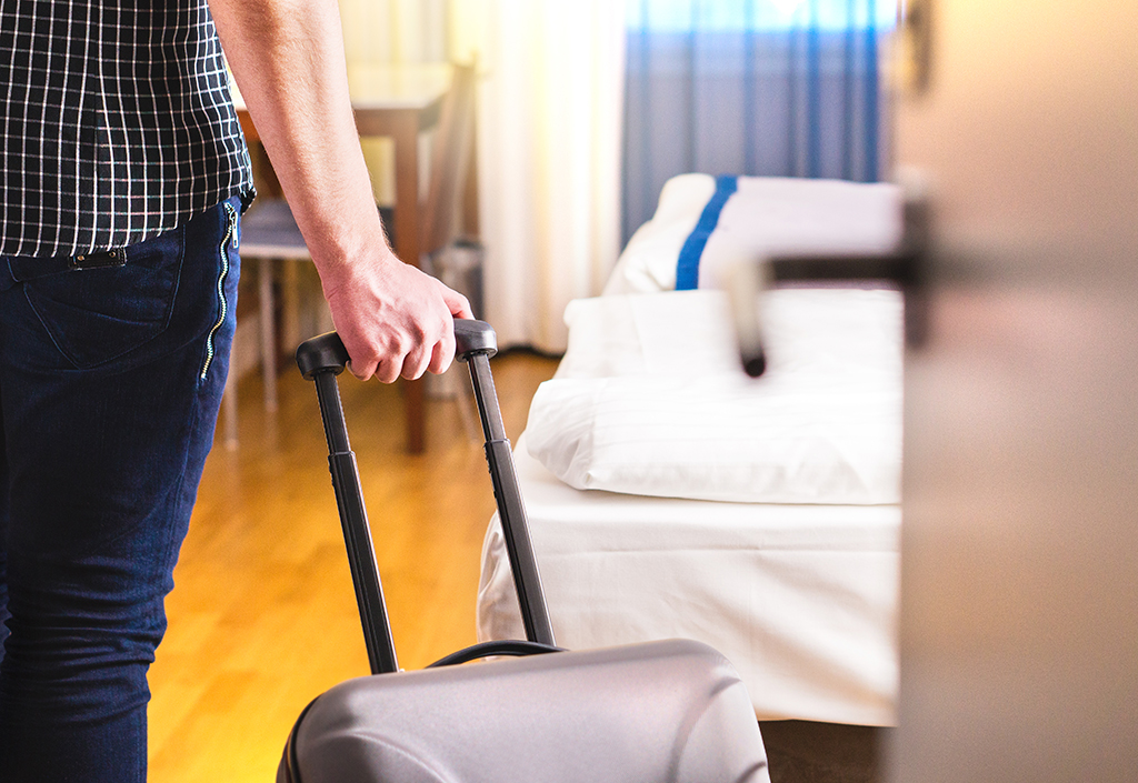 Man pulling suitcase and entering room
